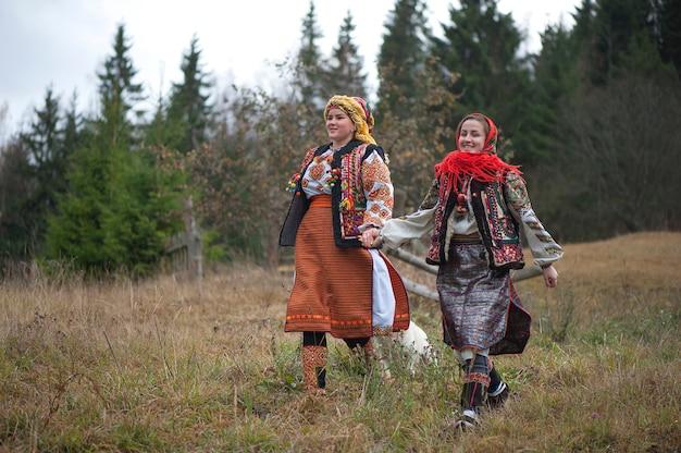 Giovani ragazze in abiti nazionali hutsul che camminano nelle montagne dei carpazi.