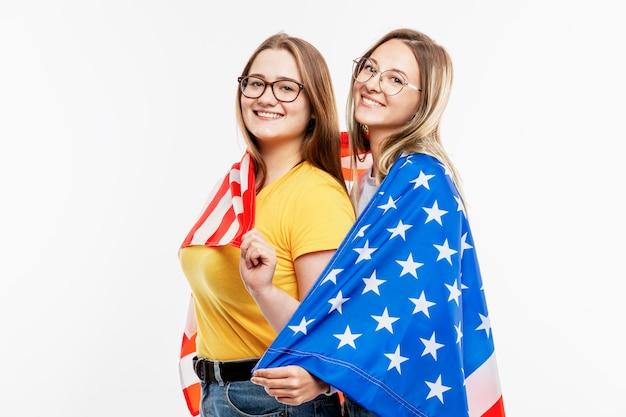 Le ragazze in jeans tengono la bandiera americana, abbracciano e ridono. celebrando la festa dell'indipendenza e il patriottismo. . spazio per il testo.