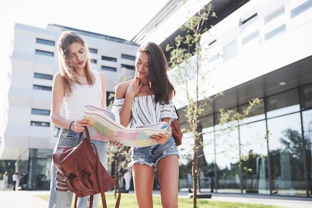Ragazze che leggono la mappa della città e cercano un hotel. i turisti adorabili con gli zaini determinano il concetto di conoscenza del mondo.