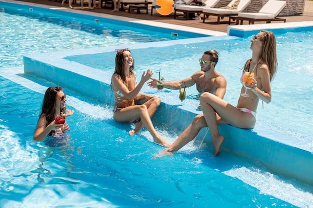 Giovani ragazze costumi da bagno e ragazzo sono seduti sul lato della piscina a bere cocktail e giocare a palla all'aperto in una soleggiata giornata estiva vicino alla zona lounge con lettino prendisole