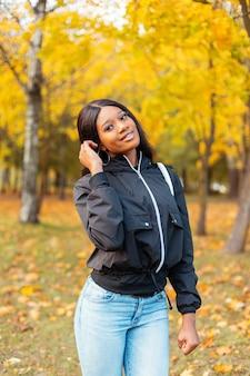 Giovane donna canadese nera alla moda glamour in giacca casual alla moda con jeans blu che cammina nel parco autunnale con fogliame giallo brillante