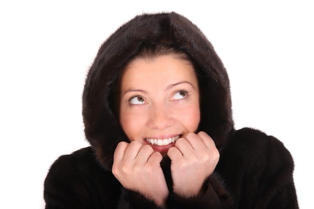 Una giovane donna glamour in un cappotto di visone che guarda in alto su sfondo bianco
