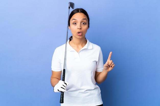 La giovane donna del giocatore di golf sopra la parete variopinta che intende realizzare la soluzione mentre solleva un dito su