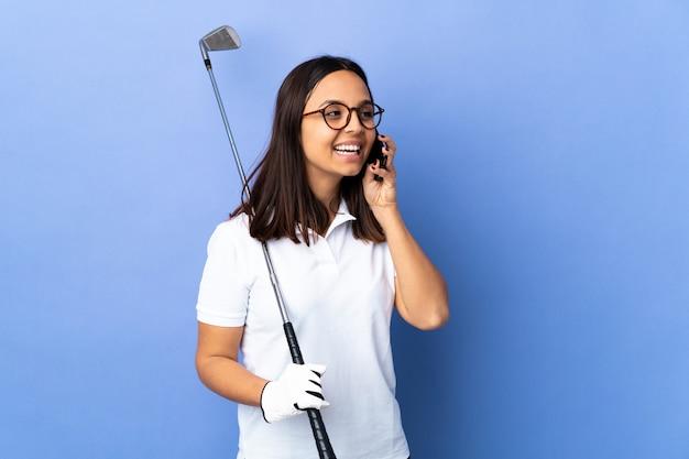 Donna giovane giocatore di golf sul muro colorato mantenendo una conversazione con il telefono cellulare