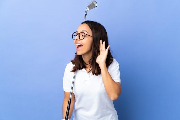 Giovane donna del giocatore di golf sopra la parete variopinta che ascolta qualcosa mettendo la mano sull'orecchio