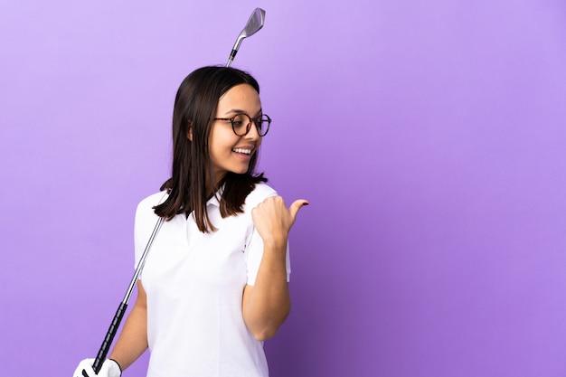 Giovane donna golfista sul muro colorato che punta verso il lato per presentare un prodotto