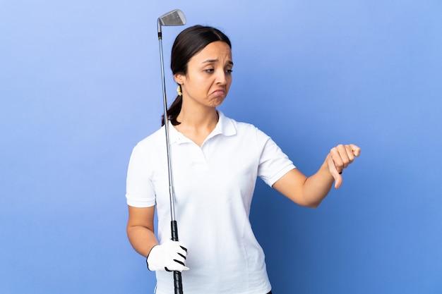 Giovane donna del giocatore di golf sopra la parete variopinta che mostra pollice giù con l'espressione negativa