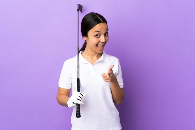 Giovane donna del giocatore di golf sopra la parete variopinta sorpresa e indicando parte anteriore
