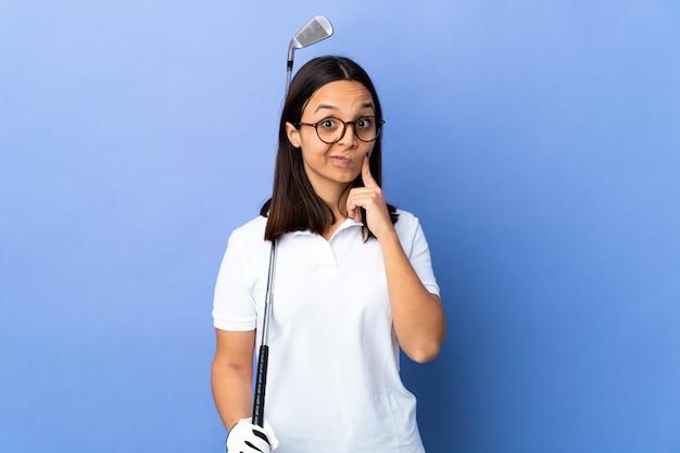 Giovane donna del giocatore di golf sopra la parete variopinta e pensare