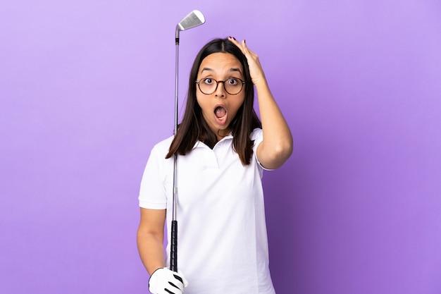 Giovane donna del giocatore di golf sopra fondo variopinto isolato che fa gesto di sorpresa mentre guardando al lato