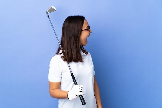 Giovane donna del giocatore di golf sopra fondo variopinto isolato che ride nella posizione laterale