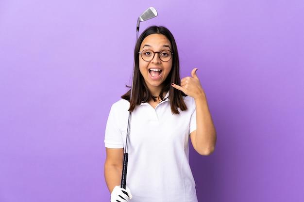 Giovane donna del giocatore di golf sopra fondo variopinto isolato che fa gesto del telefono. richiamami segno