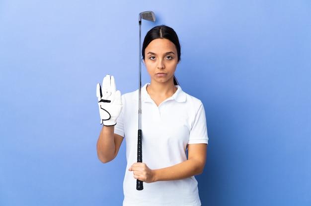 Giovane donna del giocatore di golf sopra il fondo variopinto isolato che fa gesto di arresto e deludente