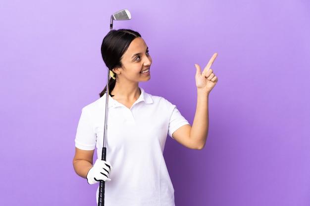 Giovane donna del giocatore di golf sopra fondo variopinto isolato che indica con il dito indice una grande idea