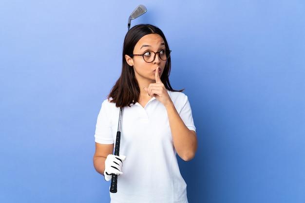 Giovane donna del giocatore di golf sopra fondo variopinto isolato che mostra un segno del gesto di silenzio che mette il dito in bocca