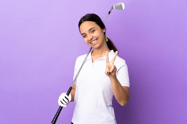 Giovane donna del giocatore di golf sopra fondo variopinto isolato che sorride e che mostra il segno di vittoria