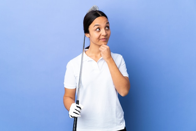 Giovane donna del giocatore di golf sopra fondo variopinto isolato che pensa un'idea mentre cercando