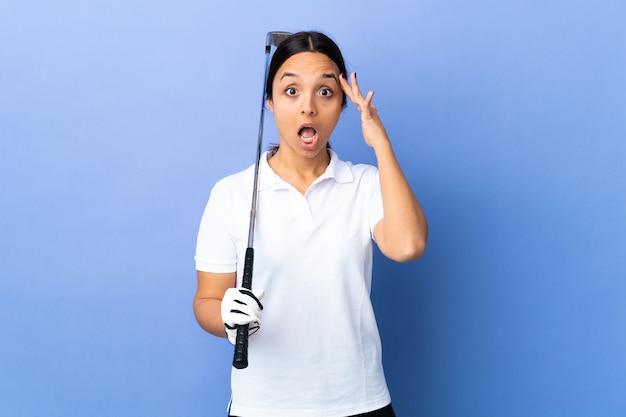 Giovane donna del giocatore di golf sopra fondo variopinto isolato con l'espressione di sorpresa