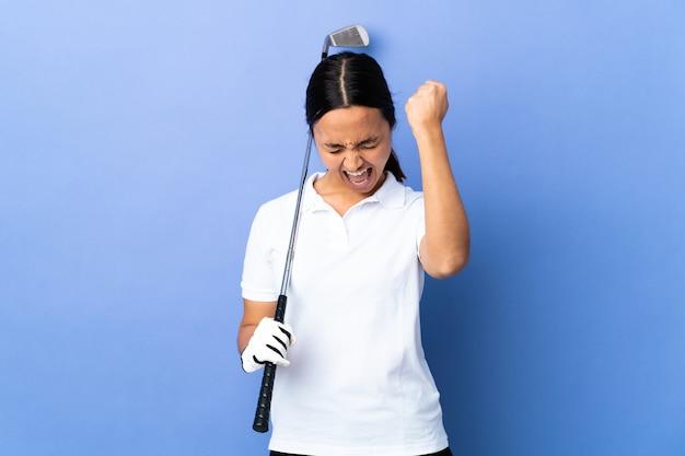 Giovane donna del golfista sopra la parete variopinta isolata che celebra una vittoria