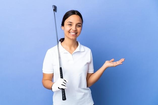 Giovane donna del golfista sopra la parete variopinta isolata che tiene il copyspace immaginario sul palmo per inserire un annuncio