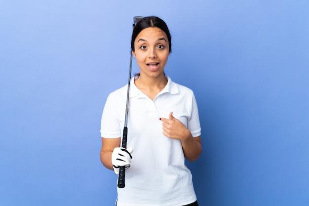 Giovane donna del giocatore di golf sopra la parete variopinta isolata con l'espressione facciale di sorpresa