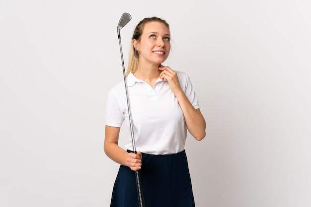 Giovane donna del giocatore di golf sopra la parete bianca isolata che pensa un'idea