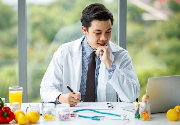 Medico giovane e di bell'aspetto che sfoglia i dati sul netbook e riempie la tabella negli appunti mentre è seduto alla scrivania con cibo sano nell'ufficio della clinica moderna
