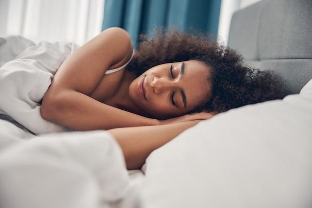 Giovane bella donna pacifica che dorme su un lato nel letto