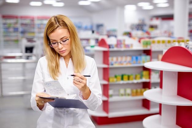 Giovane farmacista di bella donna alla ricerca di farmaci sugli scaffali della farmacia