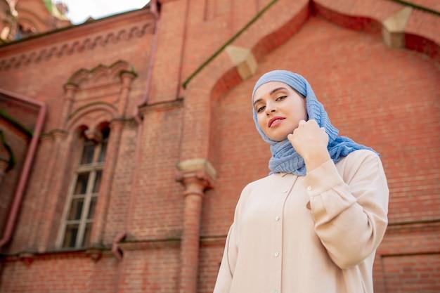 Giovane splendida donna araba in piedi sul muro dell'esterno del tempio orientale durante il viaggio nella città antica