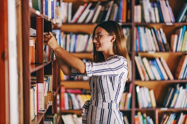 Giovane studentessa splendida in piedi accanto agli scaffali dei libri e alla ricerca del libro per gli esami.