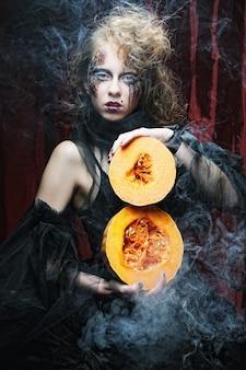 Giovane donna gotica con le zucche