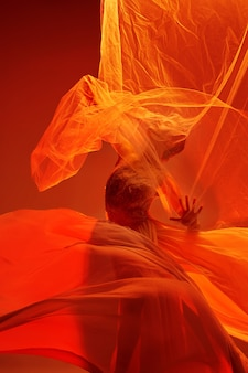 Giovane ballerino femminile grazioso o ballerina classica che balla allo studio rosso. modello caucasico su scarpe da punta