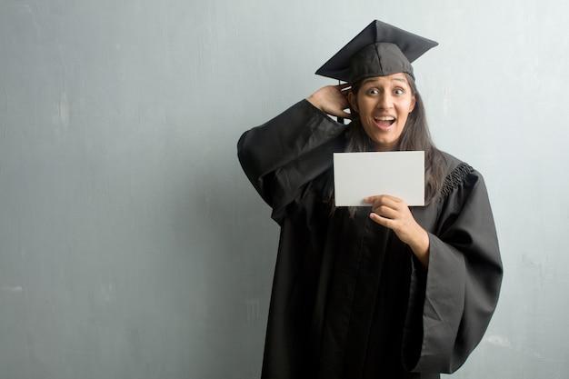 Giovane donna indiana laureata contro un muro sorpreso e scioccato, guardando con gli occhi spalancati