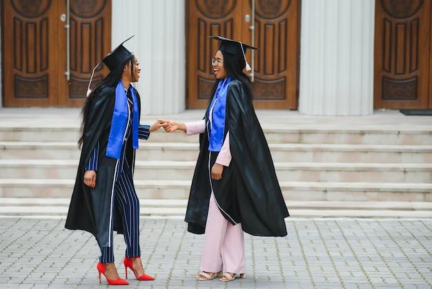 Giovani laureati in piedi davanti all'edificio universitario il giorno della laurea