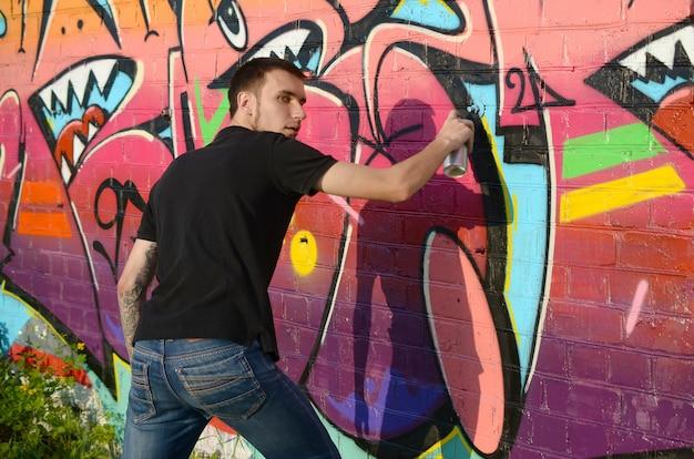 Il giovane artista dei graffiti con lo zaino e la maschera antigas sul suo collo dipinge i graffiti variopinti nei toni rosa sul muro di mattoni