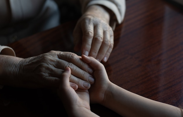 Giovane nipote che si prende cura della nonna con tenerezza e cura. mani rugose di una donna molto anziana e mani giovani di una donna adolescente da vicino, il cambiamento della generazione familiare. sanità e benessere.