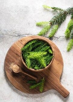 Giovani punte di abete verde in una ciotola di legno e cucchiaio con zucchero naturale