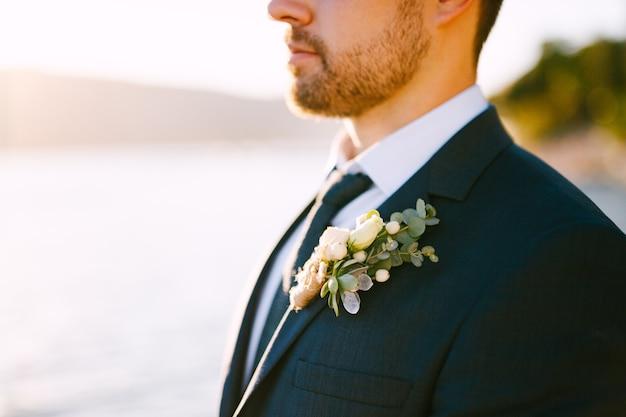 Giovane sposo in un vestito elegante con un fiore all'occhiello sotto la luce del sole