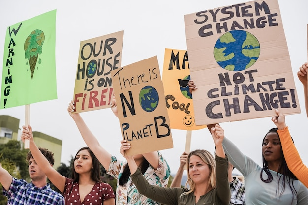Giovane gruppo di manifestanti su strada di diversa cultura e lotta razziale per il cambiamento climatico - focus sul volto di una ragazza africana