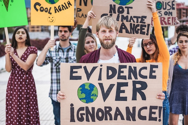 Giovane gruppo di manifestanti su strada di diversa cultura e razza lotta per il cambiamento climatico - focus principale sullo striscione