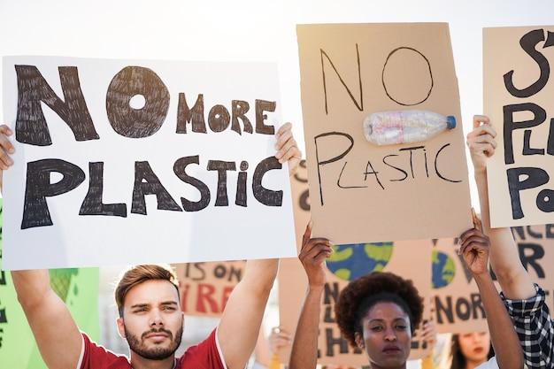Giovane gruppo di manifestanti su strada di diversa cultura e lotta razziale per l'inquinamento da plastica e il cambiamento climatico - focus on man face