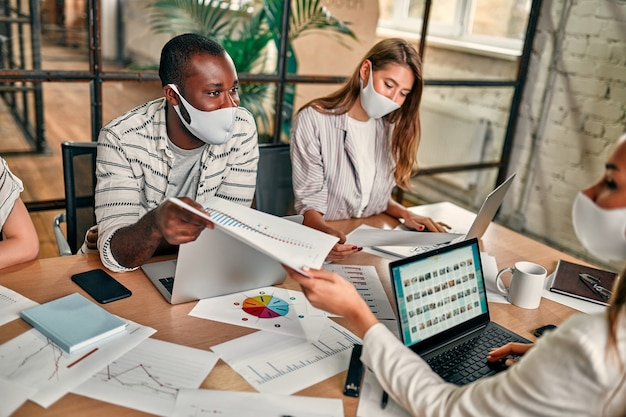 Un giovane gruppo di persone con maschere protettive è seduto con i laptop in ufficio e discute.