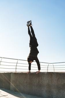 Giovane ragazzo di 20 anni in tuta nera che fa acrobazie e salta durante l'allenamento mattutino in riva al mare
