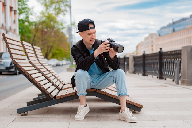 Berretto nero da giovane ragazzo, uomo con fotocamera centro città metropoli scatta foto. cattura i momenti di vacanza durante il viaggio, il fotografo scatta foto