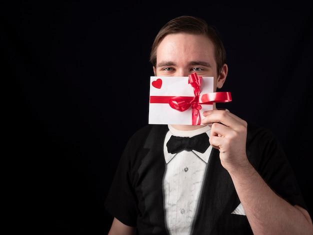Giovane ragazzo in un vestito di t-shirt nera tiene una cartolina bianca davanti alla sua faccia su uno sfondo nero