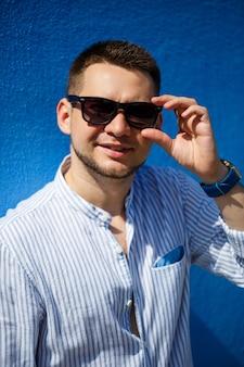 Giovane uomo d'affari con una camicia blu e occhiali neri su sfondo blu