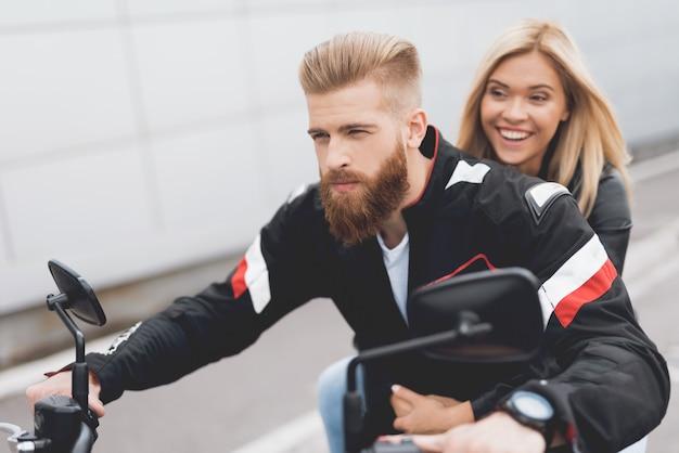Giovane ragazzo e ragazza seduta su una moto.