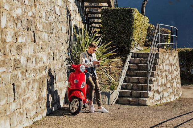Giovane ragazzo che tiene un telefono cellulare sulla motocicletta rossa.
