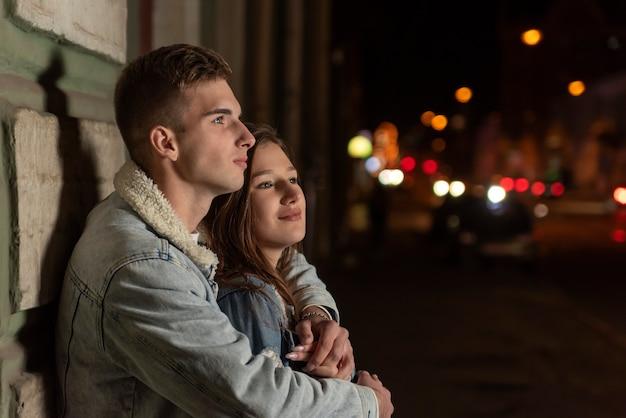 Il giovane ragazzo abbraccia la sua amata sullo sfondo della città notturna. bella giovane coppia in un appuntamento romantico serale.